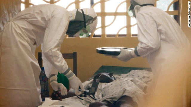 In this 2014 photo provided by the Samaritan's Purse aid organization, Dr. Kent Brantly, left, treats an Ebola patient at the Samaritan's Purse Ebola Case Management Center in Monrovia, Liberia. On Saturday, July 26, 2014, the North Carolina-based aid organization said Brantly tested positive for the disease and was being treated at a hospital in Monrovia. (AP Photo/Samaritan's Purse/AP)