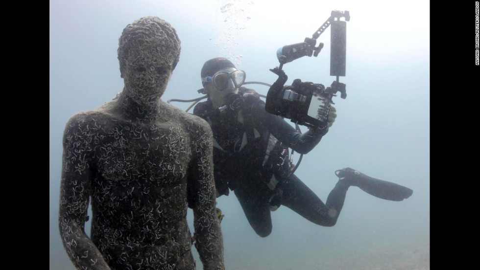 A diver takes a selfie with a replica Greek sculpture Thursday, July 24, at the Historical Underwater Park in Mali Losinj, Croatia.