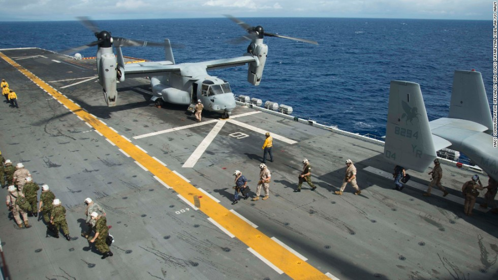 People walk past a U.S. Marine Corps Osprey aircraft aboard the amphibious assault ship USS Peleliu on July 14.