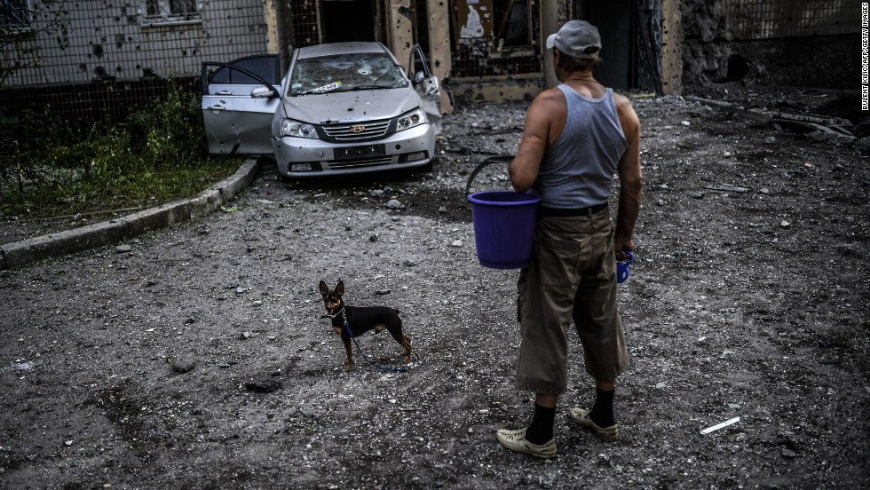 "A man with his dog looks at damage caused by shelling in Donetsk, Ukraine, on July 29. <a href=""http://www.cnn.com/2014/07/31/world/europe/ukraine-crisis/index.html"" target=""_blank"">The ongoing crisis in the Ukraine</a> has garnered international attention, especially as it has hampered the investigation over the downing of Malaysia Airlines Flight 17."