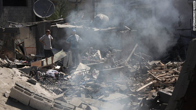 Palestinians inspect a destroyed house in the heavily bombed Gaza City neighborhood of Shijaiyah, close to the Israeli border, Friday, Aug. 1, 2014.