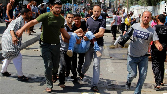 Palestinians carry a person killed in a blast outside a U.N. run school in Rafah, in southern Gaza, on Sunday, August 3.