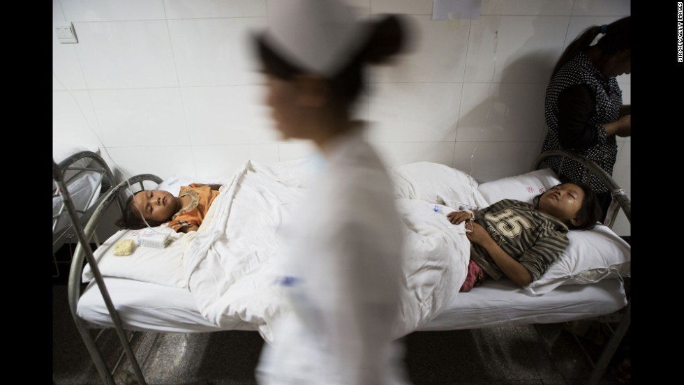 A nurse walks past two injured children at a hospital in Zhaotong on Sunday, August 3.