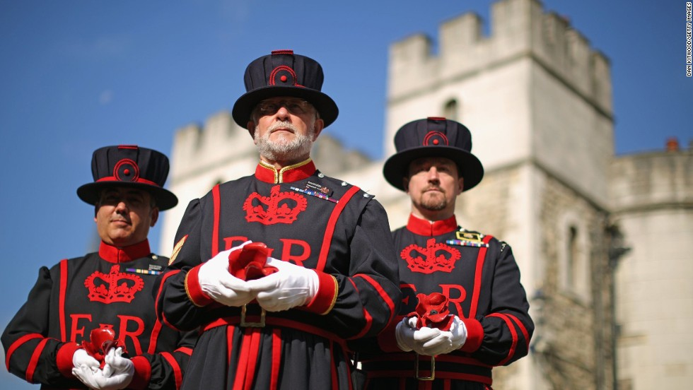 Crawford Butler, center, the longest serving Yeoman Warder at the Tower of London, poses here with the first poppy to be planted at the installation. Work on the project began on July 17, 2014.