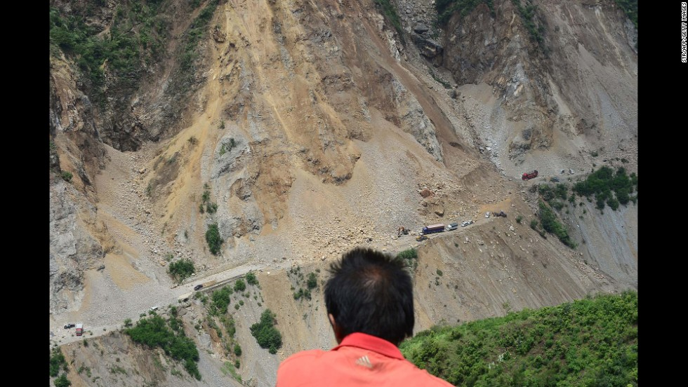 A man looks at a road buried by a landslide in Zhaotong, China, on Monday, August 4, a day after the earthquake.