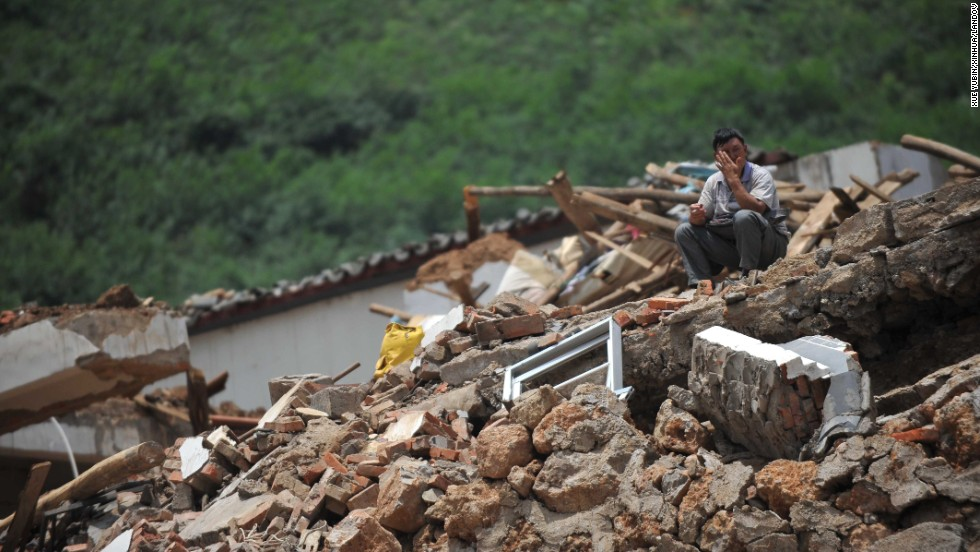 A man sits on the rubble of a collapsed house in Longtoushan on August 5.