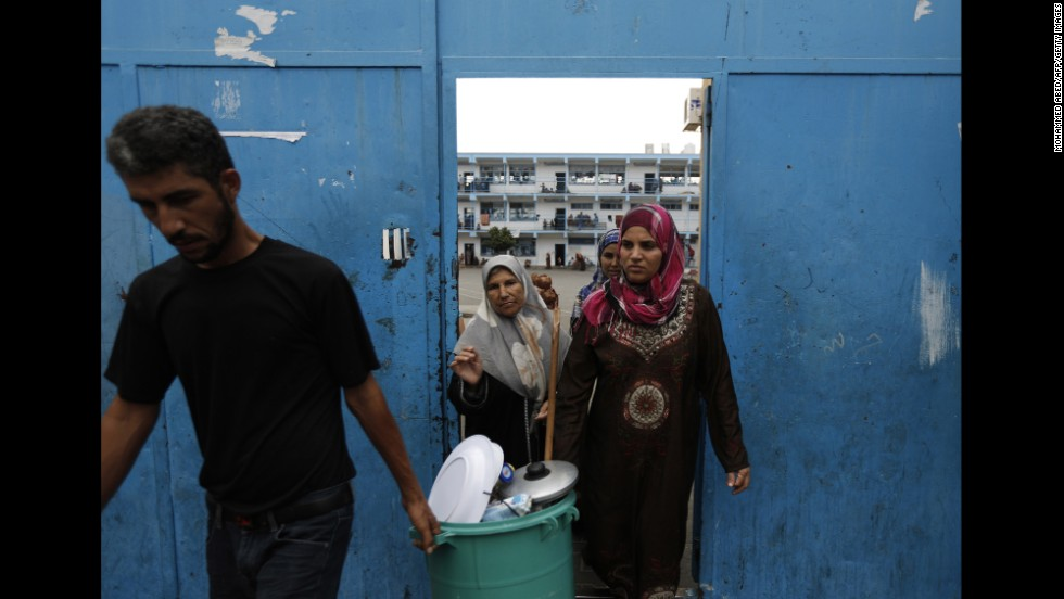 Displaced Palestinians carry their belongings as they leave a United Nations school in Beit Lahiya, Gaza, to return to their homes Tuesday, August 5.