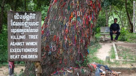 A Cambodian man sits in Choeung Ek Killing Fields near a tree that was used to beat children to death under the Khmer Rouge regime, on August 6, 2014 in Phnom Penh, Cambodia.