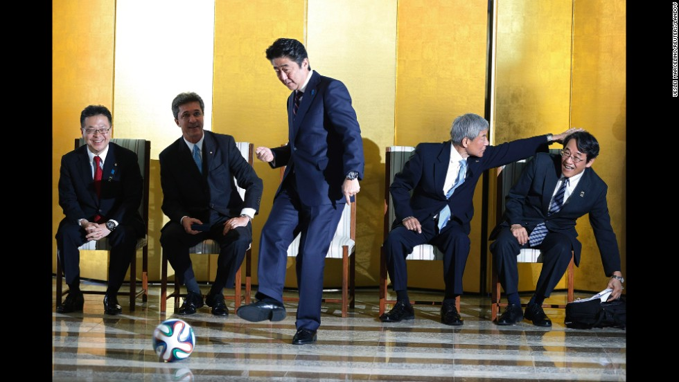 Japanese Prime Minister Shinzo Abe kicks a soccer ball during a meeting with soccer players Friday, August 1, in Brasilia, Brazil.