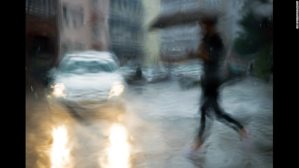 A woman with an umbrella crosses a street in Hanover, Germany, on Monday, August 4. This photo was taken through the rain-drenched window of a car.