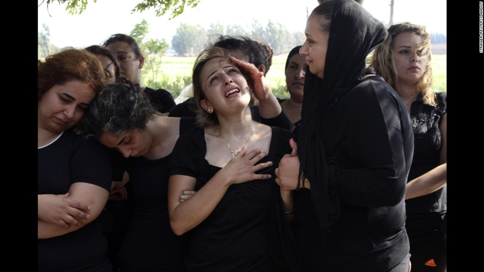 Relatives of Alawite soldier Ali Khaddaaro, who was killed during clashes between Lebanese Army soldiers and Islamist militants in Arsal, Lebanon, mourn during his funeral Tuesday, August 5, in Akkar, Lebanon.