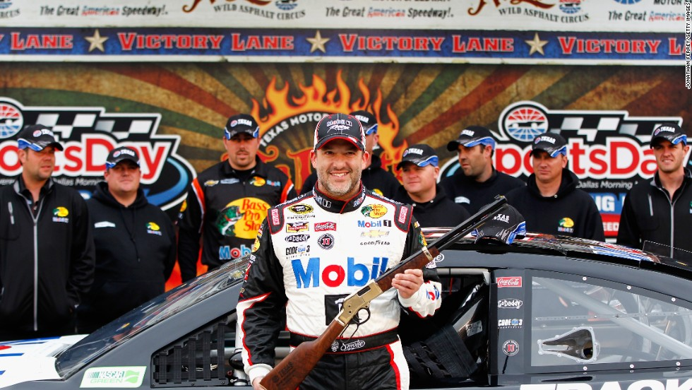 Stewart poses with a rifle awarded to him after qualifying for pole position at a race in Fort Worth, Texas, in April 2014.