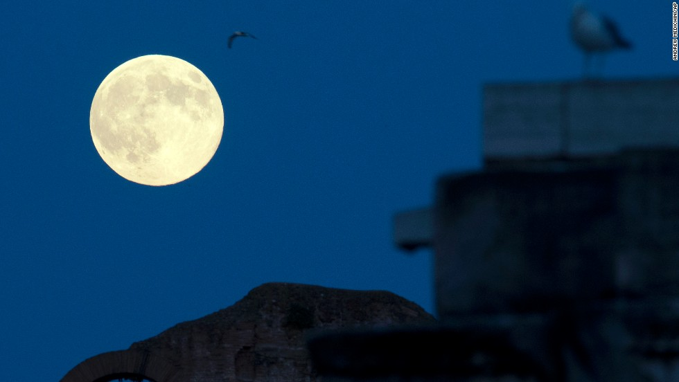 The moon appears above the Colosseum in Rome.