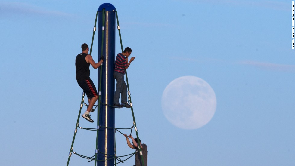Men play on a climbing structure at Riverview Park in Mesa, Arizona, while the moon rises August 9.