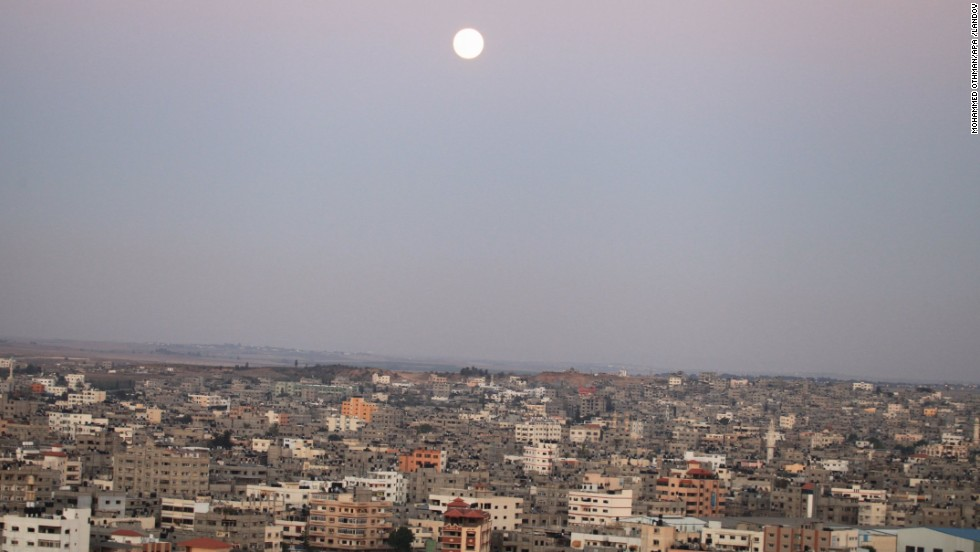 The moon rises over Gaza City.
