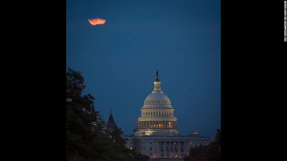 The moon appears behind clouds over the U.S. Capitol in Washington.