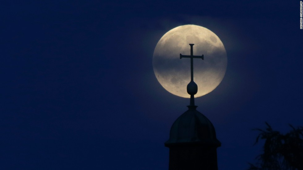 The moon appears behind a cross of the Christkoenig Church in Munich, Germany.