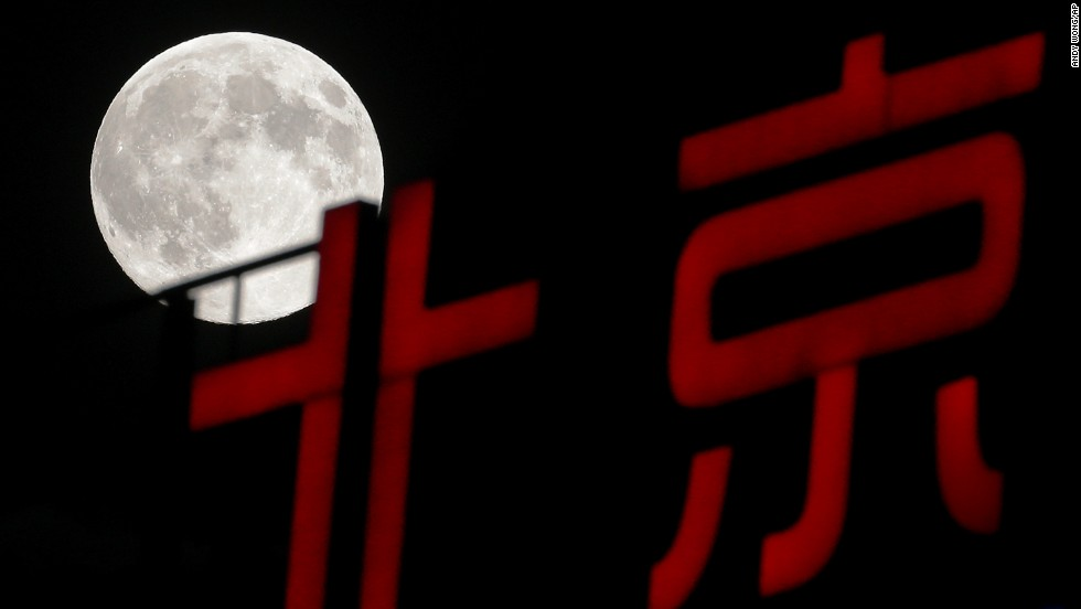 The moon rises over a sign in Beijing on August 10.