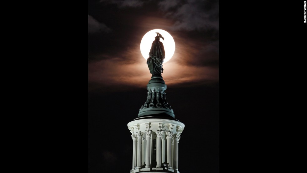 The moon rises through clouds behind the bronze Statue of Freedom by Thomas Crawford atop the U.S. Capitol in Washington.