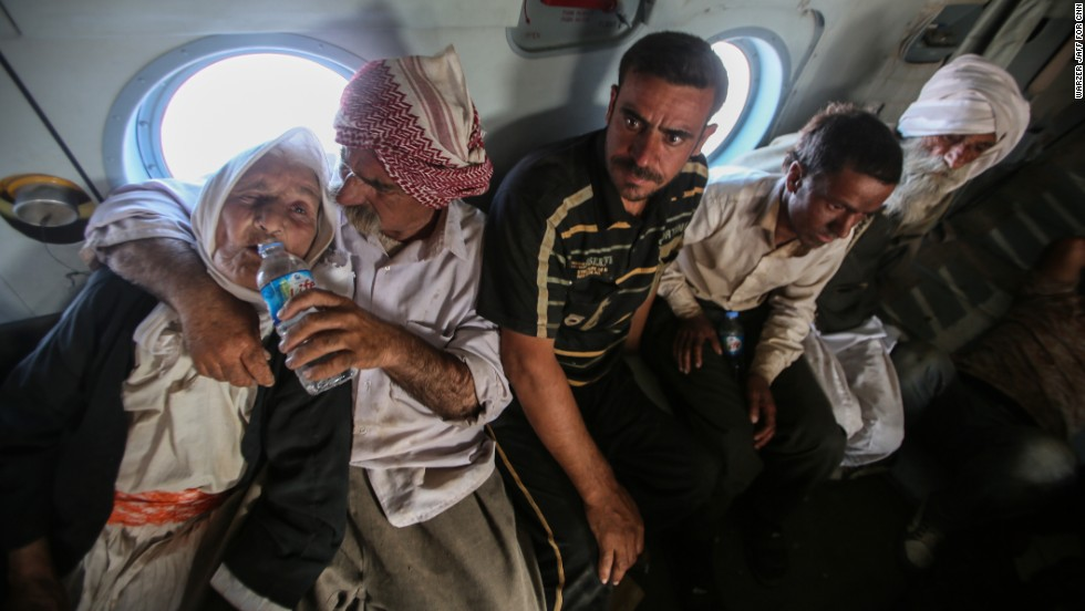 Rescued civilians sit on the helicopter.