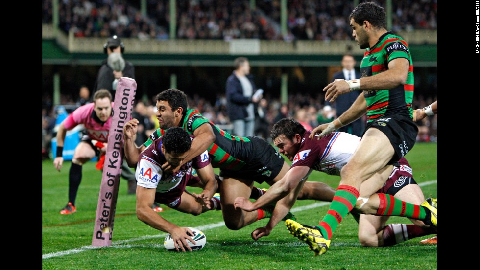 Peta Hiku of the Manly-Warringah Sea Eagles scores a try as he is tackled by Alex Johnston of the South Sydney Rabbitohs during an Australian Football League match Friday, August 8, in Sydney. The Rabbitohs won 23-4.