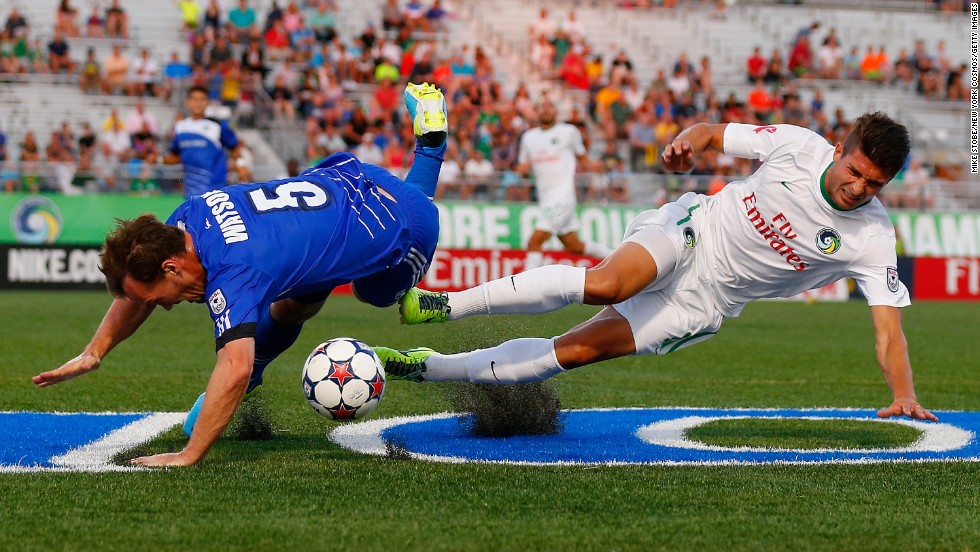 Stefan Dimitrov of the New York Cosmos, right, and Albert Watson of FC Edmonton trip as they battle for the ball Wednesday, August 6, in Hempstead, New York. The two teams play in the North American Soccer League, the second division of American soccer.
