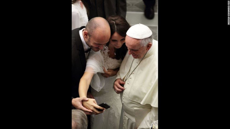 Two people at the Vatican snap a photo with Pope Francis on Wednesday, August 6.