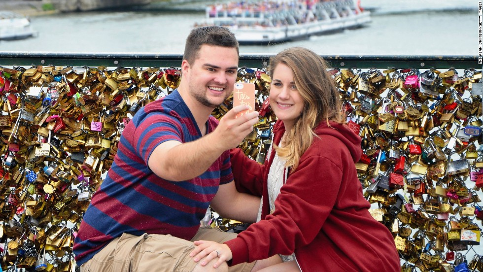 "A couple takes a selfie at the Pont des Arts bridge in Paris on Monday, August 11. The bridge sits over the Seine River and offers a fantastic view of the Paris skyline. It is also known for the <a href=""http://www.cnn.com/2014/03/31/travel/paris-love-locks/"">love locks</a> that people leave on its fence. Couples will often write their initials or names on the locks, attach them to the bridge and then throw the keys overboard to symbolize forever love."