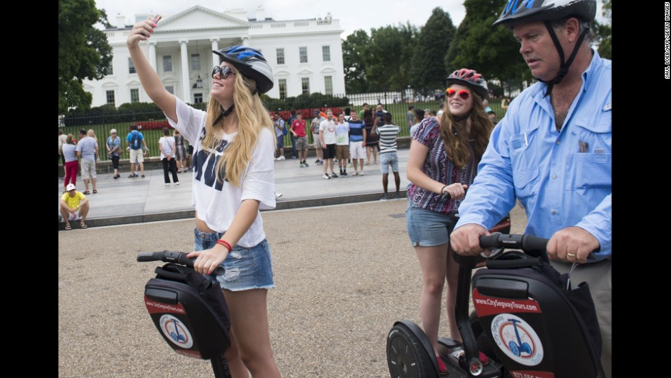 A tourist rides a Segway while taking a selfie Monday, August 11, in front of the White House in Washington.