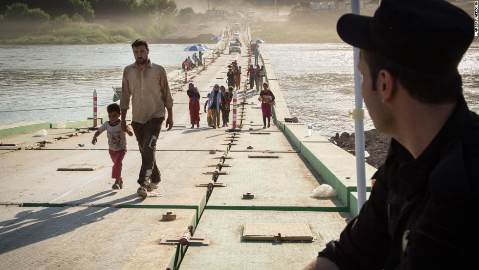 A Kurdish border guard watches while people cross.