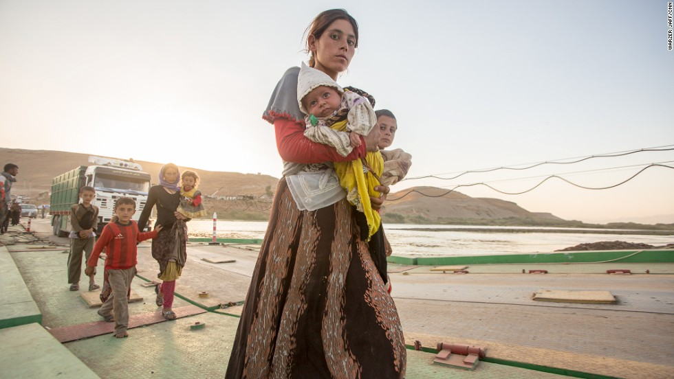 A Yazidi woman holds her baby while crossing Peshkhabour bridge from Syria back into Kurdish-controlled Iraq on Tuesday, August 12.