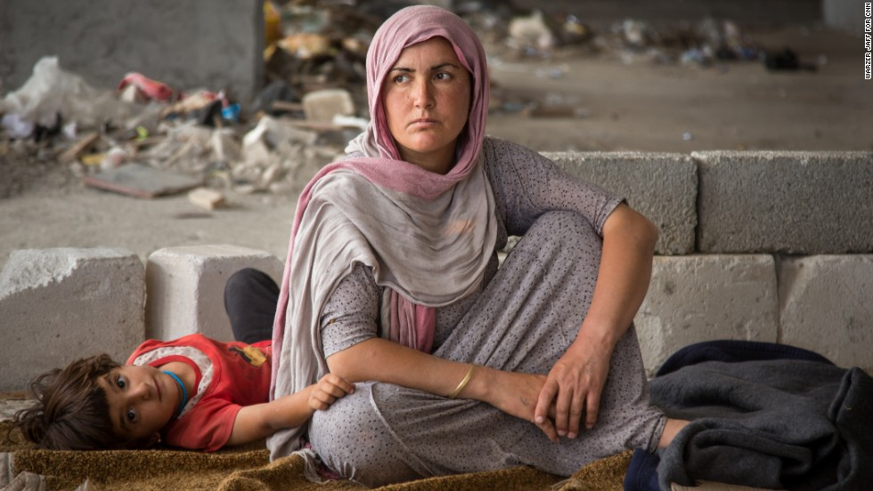 A woman and child sit in the makeshift housing on Thursday.