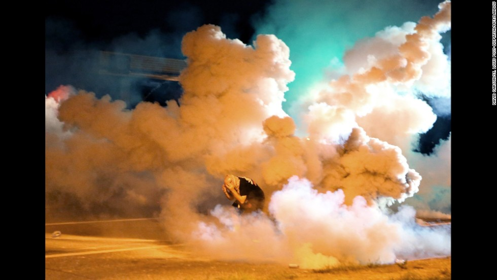 A protester runs from tear gas exploding around him on August 13, 2014.