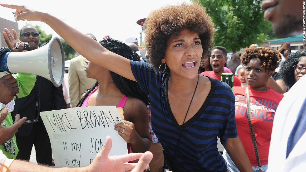 A woman tries to calm an emotional protester during a demonstration outside the headquarters of the Ferguson Police Department on August 11, 2014.