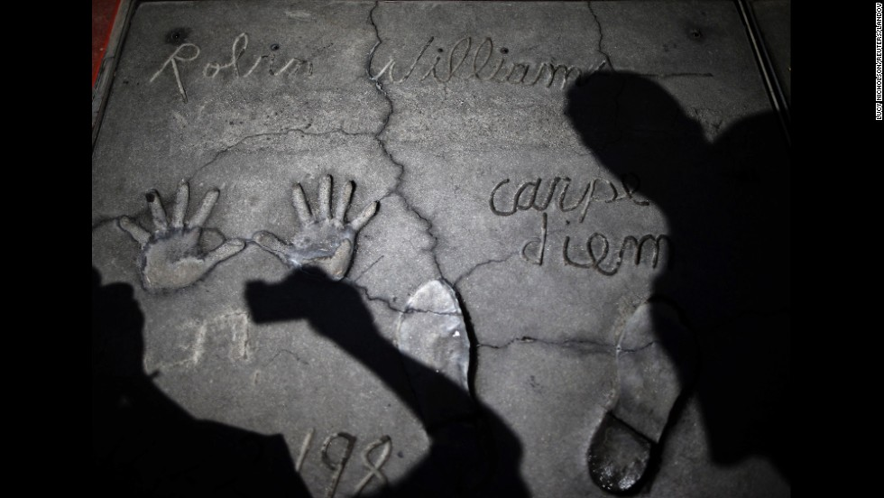 "People in Los Angeles photograph Robin Williams' handprints and footprints at TCL Chinese Theater on Tuesday, August 12. The 63-year-old <a href=""http://www.cnn.com/2014/08/11/showbiz/gallery/robin-williams/index.html"">actor and comedian</a> was found dead at his Northern California home a day earlier. <a href=""http://www.cnn.com/2014/08/14/showbiz/robin-williams-parkinsons-disease/index.html"">Investigators suspect</a> it was suicide."