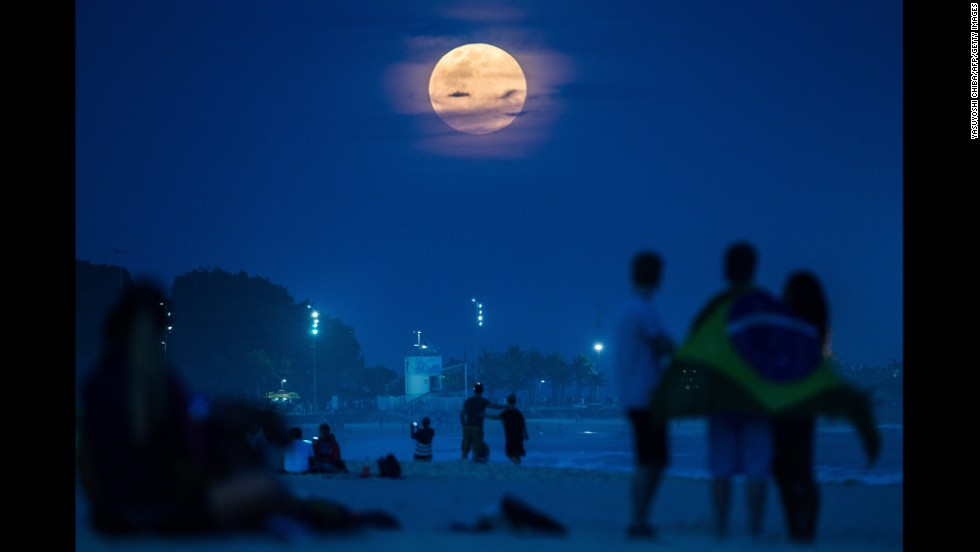 "People watch a full moon known as a ""supermoon"" Sunday, August 10, at Ipanema Beach in Rio de Janeiro. <a href=""http://www.cnn.com/2014/08/10/world/gallery/supermoon-0810/index.html"">Supermoons</a> happen when the moon becomes full on the same day as its perigee -- the point in the moon's orbit when it's closest to Earth. Full moons occur near perigee approximately every 13 months, according to NASA."