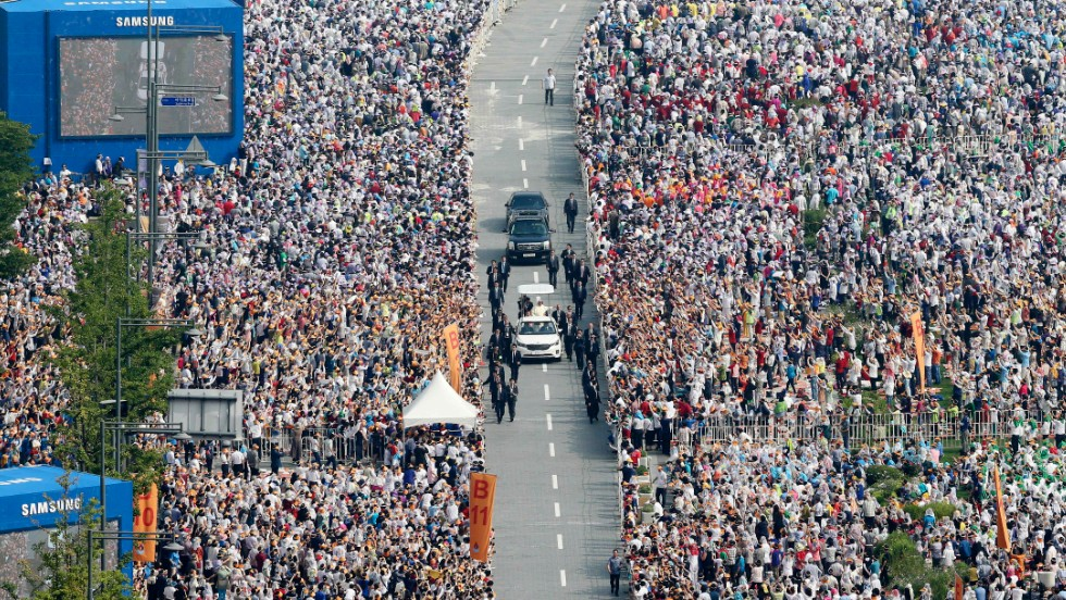 Thousands of people line a street as Pope Francis arrives for a Mass to beatify Korean martyrs on August 16.