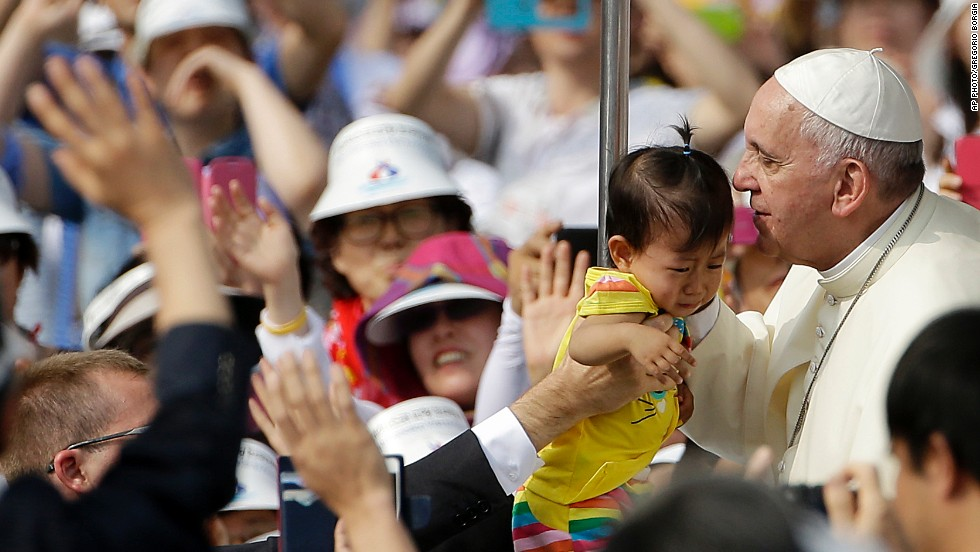 Pope Francis kisses a baby as he arrives to celebrate Mass and the beatification of Paul Yun ji-Chung and 123 martyrs, at Gwanghwamun Gate in Seoul on Saturday, August 16.