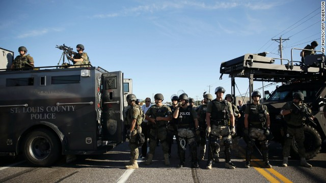 Police in riot gear watch protesters in Ferguson, Missouri, on Wednesday.