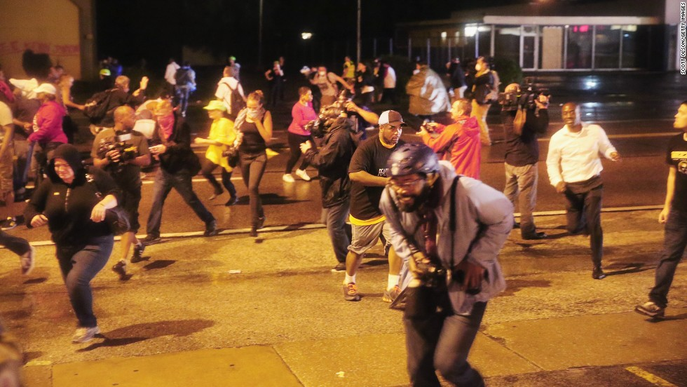 People scramble as police fire tear gas on August 17, 2014.