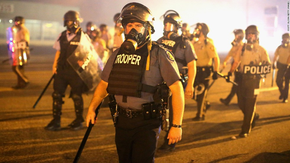 Police advance through a cloud of tear gas on August 17, 2014. Most of the crowd had dispersed after a curfew went into effect at midnight, St. Louis County authorities said.