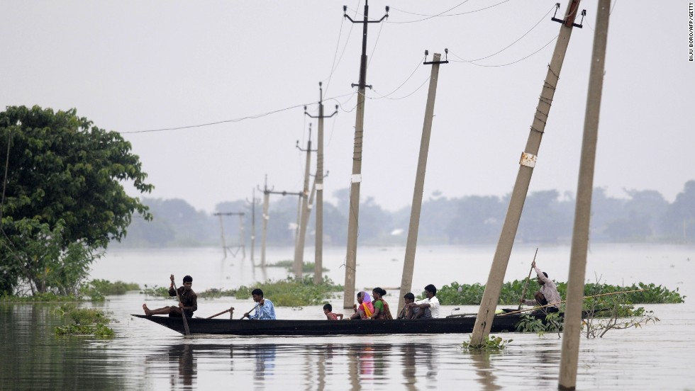 Indian villagers paddle a boat through floodwaters over submerged roads in India's Assam state on Sunday, August 17, 2014. Heavy downpours have triggered flooding that has killed at least 24 people here.