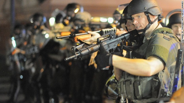 Police stand in a line with weapons drawn during a protest on West Florissant Avenue in Ferguson, Missouri, on August 18.