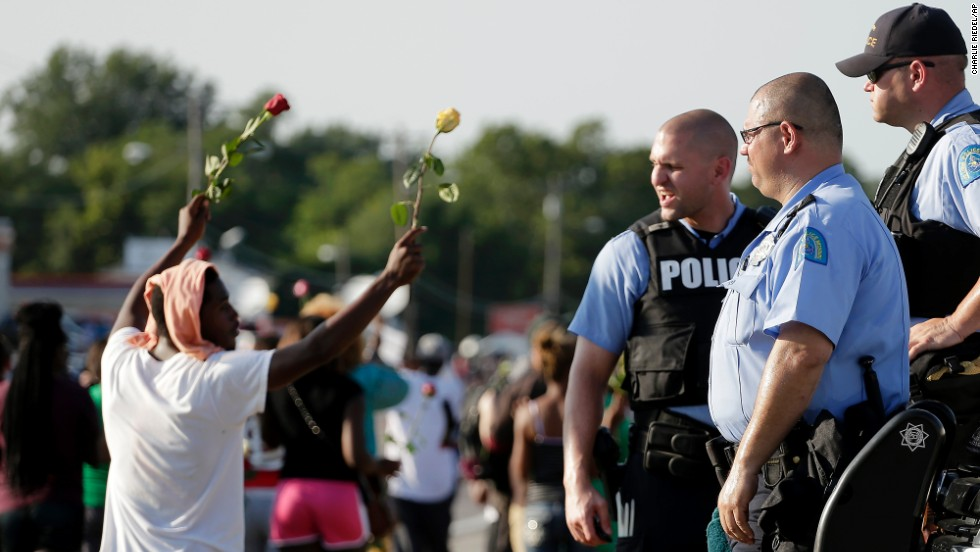 Police watch as protesters march August 19, 2014.
