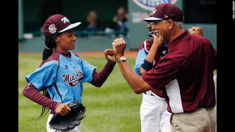 Davis, who pitches for Philadelphia's Taney Dragons, receives congratulations from coach Leland Lott as she returns to the dugout during the shutout game August 15 against South Nashville.