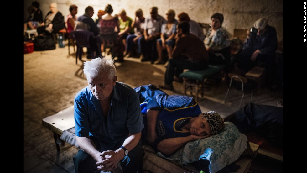 Residents sit in a makeshift bomb shelter during a shelling in Makiivka on Wednesday, August 20.