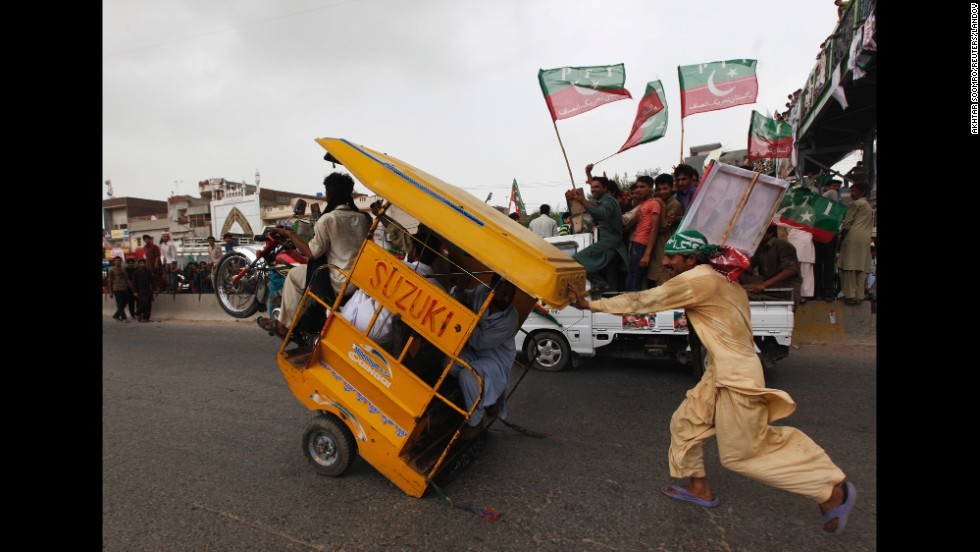 "A supporter of Pakistani politician Imran Khan runs to catch an overloaded rickshaw as he and others join <a href=""http://www.cnn.com/2014/08/15/world/asia/pakistan-khan-qadri-march/index.html"">an anti-government rally</a> in Gujrat, Pakistan, on Friday, August 15."