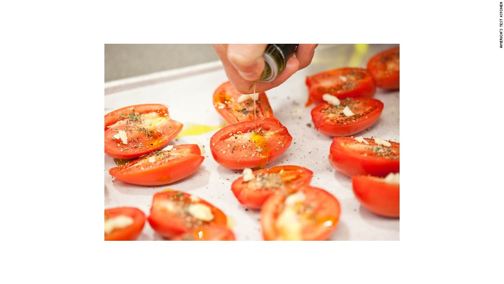 Drizzle olive oil over the tomatoes with your thumb over the spout to direct the pour.