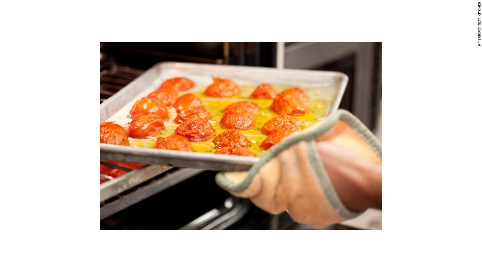 Carefully remove the tomatoes from the oven, and immediately turn the temperature down to 300 degrees. The tomatoes will have started giving up their liquid, which is why caution must be exercised when removing the trays.