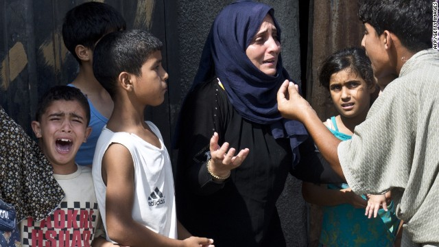 A Palestinian boy cries in panic as other members of his family discuss what to do after they ran out of their house in a hurry on August 23, 2014 in Gaza City.
